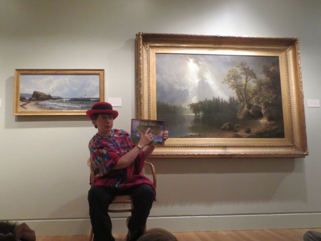 "Melody Rose Mollis Lundquist reading her book ""Oak Tree"" in the American gallery at the San Antonio Museum of Art 